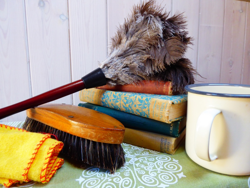 Sensory props for the story: a scrubbing brush, yellow duster, feather duster, books and a mug