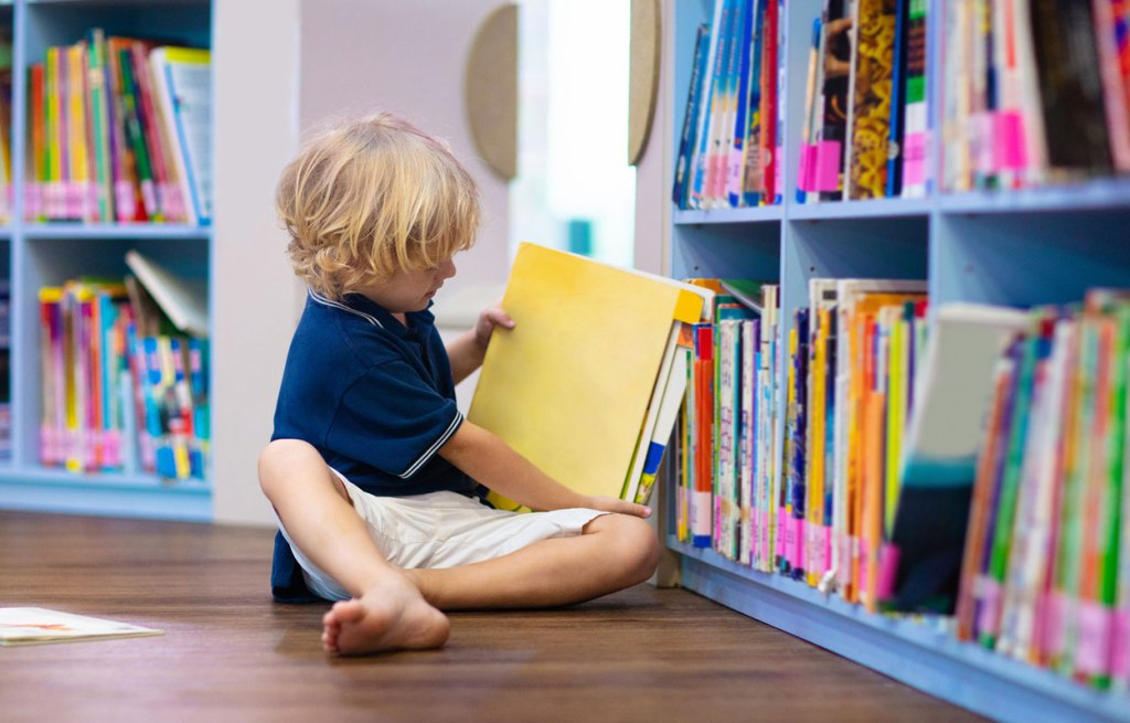 Young child in library picking out a book